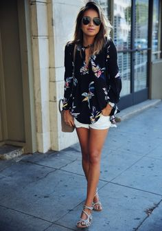 Love the floral blouse with the short white shorts.