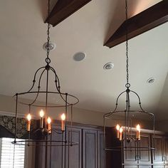 Using open chandeliers as pendants over large island for the fixer upper farmhouse kitchen look.