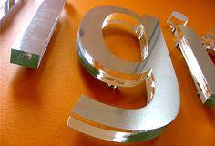 Letters uit helder acrylaat aan de voorzijde beplakt met een folie in rvs look