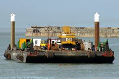 Gaverland Flatbed Sea Barge, Southern Breakwater, Dover Harbour, Kent, England, UK. Owner: Herbosch Kiere Marine Contractors. Caterpillar Tractor Company CAT crane. July 2010: Removing Spanish Prince (ex-Knight Bachelor) wreck, a First World War blockship sunk 1915. Working with Waasland Sea Barge, Haven Seafield Sea Barge, and Sarah Grey Tug. English Channel on left. View from Admiralty Pier. Port of Dover Workboat, Demolition, Salvage, and History. See…