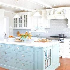 Give an all-white kitchen a lift with a refreshing coat of blue for a classic, pleasing palette with a hint of color. With a cornflower-blue island and watery-hue backsplash, this white kitchen feels cheery and full of character. #kitchen design ideas #kitchenisland