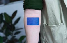 Abstract blue square tattoo on the right inner forearm.