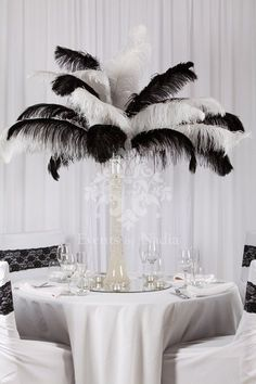 Tall 'Lily' vase filled with water crystals and with black and white feather arrangement, on round mirror base with tea lights