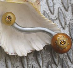 Product Name: Eel Sunflower Left Product Description: Hand sculpted drawer pull with silver metal and colored in silver, deep gold and light gold with topaz crystal Size: 5
