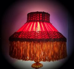 An 1880's restored English Victorian kerosene lampshade. A double red silk lining with a plumb purple chiffon pleated over top . The original metallic trim was re applied and the fringe was replaced with a hand dyed fringe to match the original as close as possible.