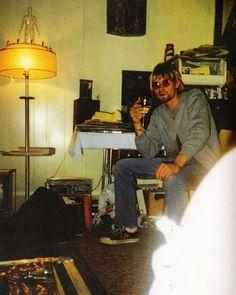 Kurt Cobain surrounded by vinyl and magazines inside his Olympia, Washington apartment, 1990.