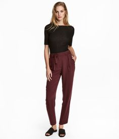 Burgundy. Loose-fit pants in airy woven fabric. Regular waist, pleats at front, hook-and-eye fastener, and tie belt. Zip fly, slightly dropped gusset, side