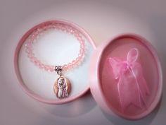 """Detalle para niñas en su primera comunión, es una pulsera elástica con bolitas de cristal rosa y colgante plateado de """"mi primera comunión""""."""