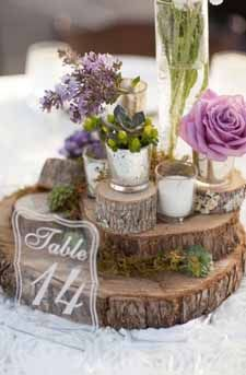 woodland wedding centrepiece ideas tree slices staked up with small vases and mercury silver tea light holders
