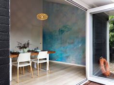 Ocean water painted contemporary abstract mural in kitchen viewed from the deck, featuring a custom built wooden table styled with kitchenware, the artwork has movement and reflects light.