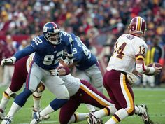 Defensive End Michael Strahan #92 of the New York Giants broke through the Washington Redskins' line in an attempt to sack Quaterback Brad Johnson #14 in a NFL game against the Washington #Redskins at FedExField on December 3, 2000 in Landover, Maryland. #nyg