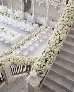 A staircase filled with flowers makes the entrance to a white wedding stunning