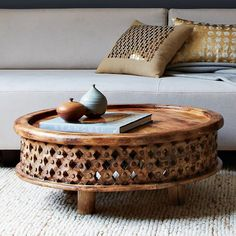 Part sculpture, part table, all artisanal. Craftspeople in Jaipur, India, hand carved the delicate rosettes on this low-lying solid mango wood table, which takes its original inspiration from a ceremonial stool used by Bamileke royalty in the African country of Cameroon.