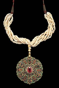 Morocco | A gemset (central red garnet set in a band of small emeralds) and enamelled gold circular pendant (Tazra), suspended on multiple seed-pearl stands. The back of the pendant is similarly enamelled | Fez, late 18th century | 45,600£ ~ sold ( Apr. '07)