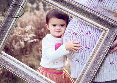 Maternity photos, little girl hugging belly with frame.  Facebook.com/amandajdesigns