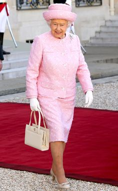 2014 The Queen stepped out in Paris in a sprightly pink skirt suit, matching topper and bow-topped pumps.
