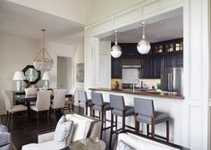 Instead of a complete open plan design, this kitchen features a large pass-through window. The dark blue cabinets are a refreshing surprise and contrast to the home's many white elements and help the small kitchen feel both sophisticated and intimate.