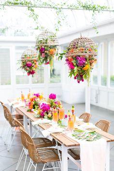 Mesa de jantar colorida, mesa de madeira com pratos brancos, talheres dourados, decorado com folhas de coqueiro e costela de Adão. Lustre de flores suspenso. Arranjo Floral. Almoço de verão com mesa tropical e lustre com flores