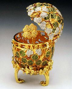 Originally presented in 1902, by Czar Nicholas II to his wife Empress Alexandra Fedorovna, the entire shell is covered with green enamel pique-a-jour green enamel and three-leaf clovers. A ribbon of ruby crystals is threaded between the clover leaves. A tripod stand, also embellished with clover leaves supports the egg. When opened the egg reveals its surprise, a 24k gold-plated four-leaf clover brooch, which can be worn.