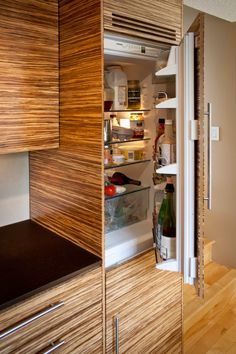 Built-in fridge.Mocha Paperstone (recycled paper countertops) with strand bamboo plywood cabinets and Stucco Italiano lime plaster walls (Venetian plaster). Supplied by GreenWorks Building Supply Vancouver, BC.