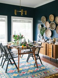 Dining Room decor ideas - modern eclectic style with dark green walls, colorful rug, pottery display wall and bronze light fixture | Becki Owens