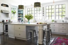 Marble countertops, casement windows, metal Marais stools, and a cup-style cabinet hardware are featured in the kitchen addition.  Click through for the full story on Tami Ramsay's home makeover!