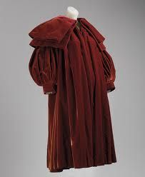 Evening coat, fall/winter 1950. Cristobal Balenciaga (Spanish, 1895–1972)This full evening coat of American Beauty red velvet has melon or pumpkin sleeves. A double circular cape collar conceals where the front is gathered at the neck and the short back yoke to which a full back is gathered. The tremendous balloon sleeves attach to a turnback cuff.