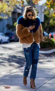 fall outfit inspiration + casual street style look + faux fur jacket with jewel tones + distressed denim + lace up booties + round sunnies