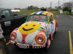 "Katherine Smith, of Jarrettsville, glued 8,000 colored ping pong balls on an old 1971 Volkswagen Beetle named ""The Last Cup"". Her art car features different scenes each section of smiley face hood peace sign on a even the hub caps and bumpers are covered with ping pong balls."