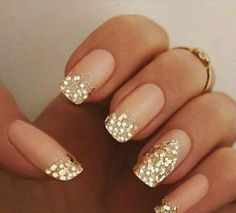 Gold silver sparkle french tip, faded gold sparkles on accent ring finger. Nude peachy soft base coat. Clean edges small extension square or squoval tips . Gel or acrylic nail ideas