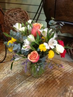 how sweet it is  large coral standard roses, white alstromeria, yellow button mums daisies, hot pink pixie carnations, baby blue eucalyptus, and purple misty in a clear glass ginger vase