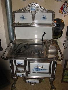 Beautiful antique Art Nouveau kitchen stove with Delft Painting and paw feet. Probably from Holland, Wood Burning Cook Stove, Wood Stove Cooking, Old Kitchen, Vintage Kitchen, Kitchen Decor, Antique Wood Stove, How To Antique Wood, Antique Art, Antique Kitchen Stoves