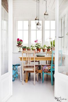 really love the white space, fun lights, colorful mismatched chairs, and geraniums!