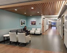 In the subwaiting area, layered woods in the low ceiling and wood floor patterns create a comfortable environment for guests and patients. Windows at the end of the express care corridor bring natural light into the space. Photo: © Jeffrey Totaro, 2014.