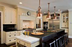 Beautiful soapstone kitchen island countertops, paired with white marble, brass light fixtures and black cabinet pulls. Very stylish blend of these hot new trends!