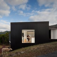 This blackened timber house sits on the hillside of a Portuguese island.