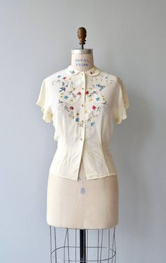 Vintage 1950s cream rayon blouse with red, blue, black and yellow hand-painted flowers and flourishes, short sleeves, prong set rhinestones, round collar and pearl buttons and waist darts. --- M E A S U R E M E N T S --- fits like: medium shoulder: 16.5 bust: 36-38 waist: fits up to 32 sleeve: 5 length: 22 brand/maker: Deb condition: excellent ➸ More tops & sweaters https://www.etsy.com/shop/DearGoldenVintage?section_id=5800171 ➸ Visit the shop http:/...
