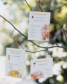 Illustrated cards listing the ingredients of each drink hung from tree branches next to the bar at this casual outdoor reception.