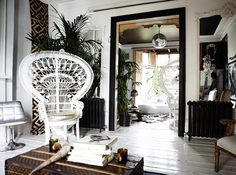 Disco ball, white peacock chair, horn on trunk coffee table, white wood floor, indoor palms, large french white mirror, black heaters. Love all the details!