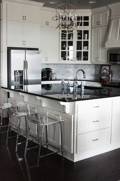 Black granite countertops and white shaker style ceiling height cabinets. Vapor stools from CB2