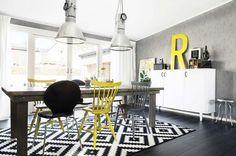Un salón de base nórdica con detalles industriales (lámparas) y vintages (sillas madera y taburete)