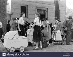 Download this stock image: The picture from a Nazi news report shows Sudeten German women and children being cared for by girls from the German League of Girls (BDM) upon arriving in a refugee camp after fleeing from Czechslovakia in September 1938, location unknown. The original Nazi propaganda text on the back of the picture reads: BDM members take care of the smallest. The minors who are housed in the assembly and refugee camps or with individual families, find loving care from members of…