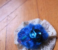 A brooch that I made years ago, lace, crochet wool and a small skull of my army in raw clay glazed in petrol blue  http://www.danael.name