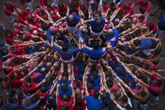 Members of the Castellers Vila de Gracia start forming their famous human tower called castell in the Barcelona neighborhood of Gracia, Catalonia, Spain on Sunday May 19 2013. A castell is a human tower traditionally built during festivals in many places in Catalonia. At these festivals, several colles or teams compete to build the most impressive towers they can. (AP Photo/Emilio Morenatti)