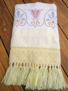 Toalha de rosto na cor amarela, bordada em ponto cruz com acabamento em macramê.