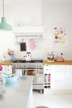 love this modern colour take on a white kitchen, green lamp & lovely wood butcher's block counter tops