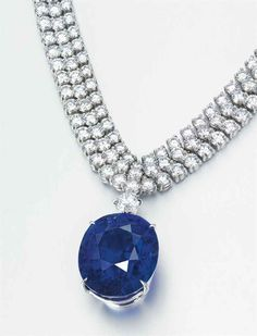 A STUNNING SAPPHIRE AND DIAMOND PENDANT NECKLACE.  The oval-shaped sapphire, weighing approximately 55.56 carats, surmounted by a circular-cut diamond, to the three-row circular-cut diamond necklace, mounted in platinum and gold, in red leather Cartier case.  Necklace signed Cartier, no. 870107.