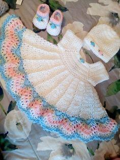 El vestido blanco del bebé del ganchillo fijó con el ajuste