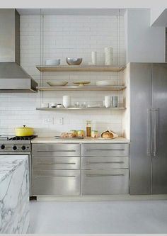 Sleek, modern white kitchen, suspended shelving. Love the suspended shelves. I could see them in a thicker wood for the cabin