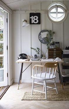 All-white, Scandi inspired Garden shed with desk and statement wooden chair. More ways to revamp your garden shed at http://www.redonline.co.uk
